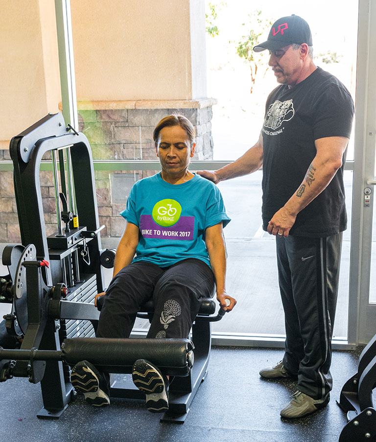 David Lyons helping someone with MS workout on a weight machine